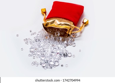 Red and gold pouch filled with small diamonds scattered on a white table on a white background. Shiny diamonds. Luxury diamonds. Diamond jewel. Beautiful transparent crystals on black background.