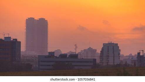 The red gold sunset over a tall city buildings