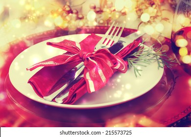 Red and gold themed holiday dinner table plate setting