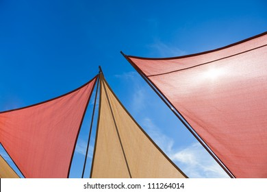 Red and gold triangle shaped netting provides shade from the summer sun with a bright blue sky background.