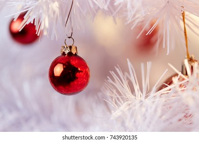 Red and Golden Christmas Balls hanging on the white branches of a christmas tree