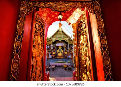 Red golden gate entrance of Wat Ming Muang against sunrays during sunset, Chiang Rai, Thailand. Traditional Lanna THai temple style, Norhern of Thailand.