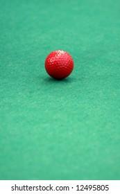 Red golf ball on a mini golf putting green