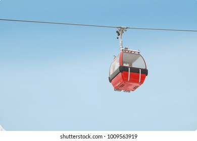 Red gondola car lift on the ski resort over forest trees