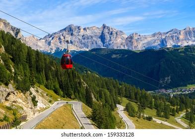 Red gondola car lift twisting road to Passo Gardena from Colfosco village, Dolomites Mountains, Italy