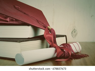 A red graduation cap resting on two books with a diploma tied with red ribbon on a wooden background. Copy space. Vintage filter added