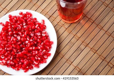 Red grains of garnet on a white plate and a glass of garnet juice on the mat