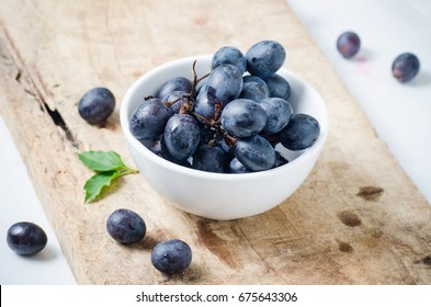 Red grape in a bowl on wooden,Healthy fruit