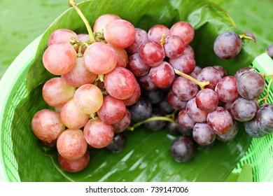 red grape on banana leaf background