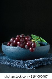 Red grapes in a blue bowl on a dark background with copy space for your text