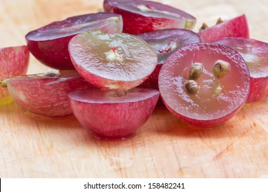 red grapes cut in half, isolated on a white background.