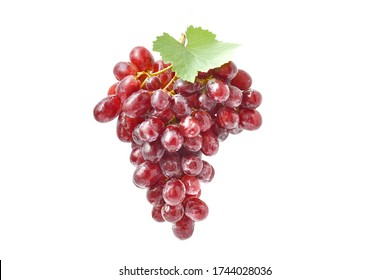 Red grapes, large fresh fruits, red, pink, with green leaves in close up on a white background