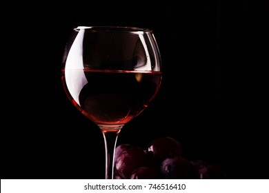 Red grapes lying on black background with wineglass