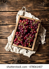 Red grapes in an old box. On wooden background.