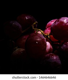 Red grapes sprinkled with water droplets in dark setting
