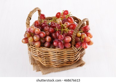 Red grapes in a woven basket on a white background close up