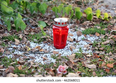 Red graveyard candle on white stony ground.