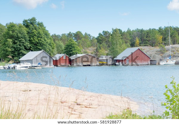 Red and gray boathouses, rock and trees in the archipelago in Aland, Finland