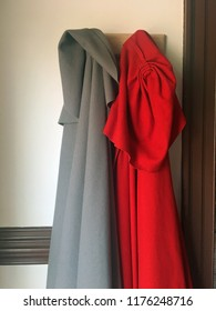 Red and gray cloaks hang in hallway