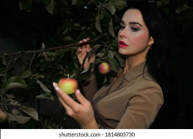 Red and green apple in female hand. woman in autumn dress is standing under apple tree and looking at a red apple. Seduction, sexuality. Women's Health. Reproduction.