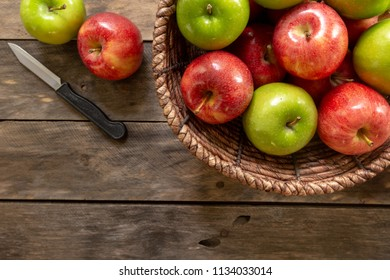 Red and green apples in basket on rustic wood table