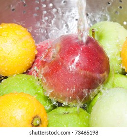 red and green apples and lemons being washed in stainless steel colander under tap