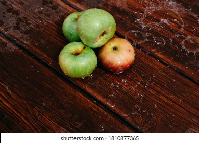 Red and green apples lie on the mahogany wooden kitchen table, and water drips from the top. Splashes of clean water pour over freshly picked apples of the autumn harvest.
