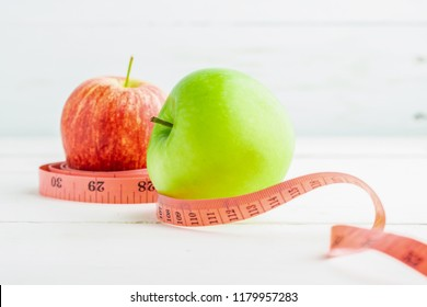 Red and green apples with measuring tape on white table