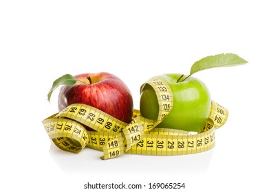red and green apples with measuring tape on a white background