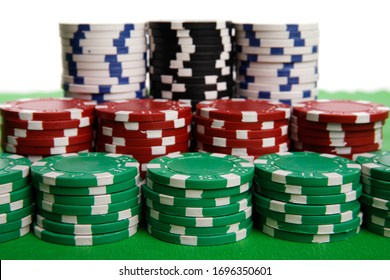 Red, green and black casino chips on green table and white background