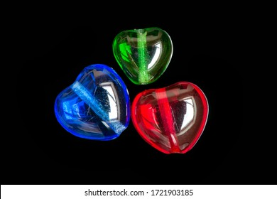 Red green blue heart shaped beads on black background