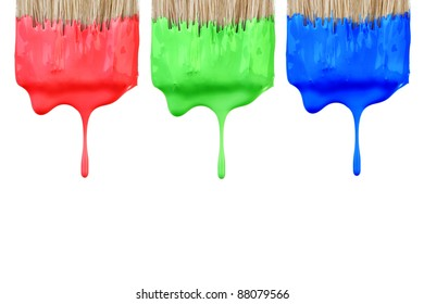 Red, green and blue paint dropping from brush isolated on white background. Graphic design creativity concept.