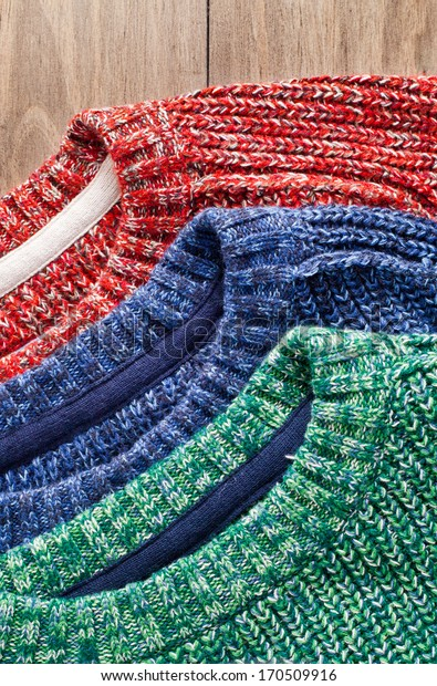 Red, green and blue wool jerseys stacked on a wooden surface