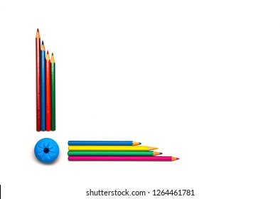 Red, green, blue, yellow, orange, purple pencils and blue sharpener isolated on white. Borders and frames concept. Back to school. Empty background with lot of space for text, advertising design.