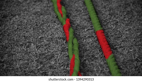 Red and green boundary ropes on a grassy ground