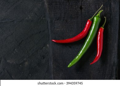 Red and green chili peppers on black wooden cutting board over black plastered background. Top view.