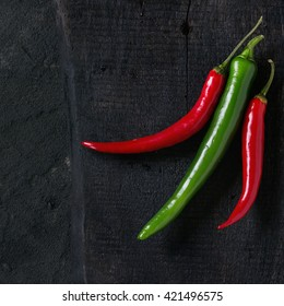 Red and green chili peppers on black wooden cutting board over black plastered background. Top view. Square image