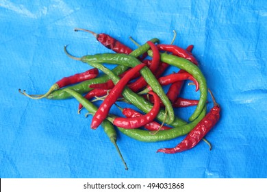 Red and Green Chilies on Blue Mat