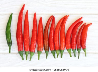 Red and green chilis on white wooden background.