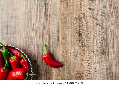 Red and green chilli pepper in a dish on wooden table with copy space