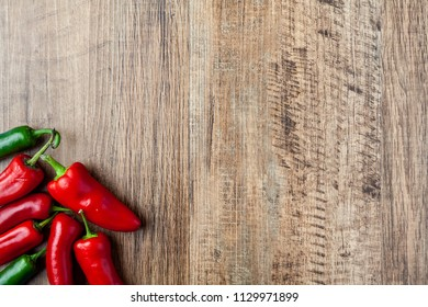 Red and green chilli pepper on wooden table with copy space