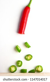 Red and green chilli peppers cut into pieces isolated on a white background