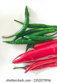 Red and green chilli peppers on a white surface