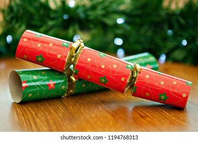 Red and green Christmas crackers, on a wooden table with evergreen garland behind the crackers.