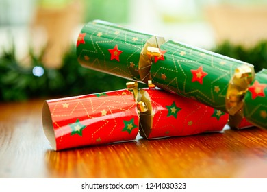 Red and green christmas crackers with stars closeup, with a bokeh background