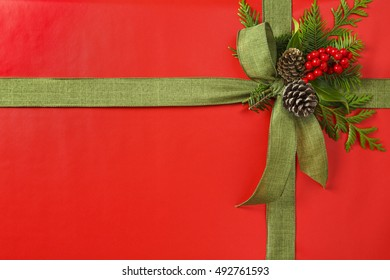 Red and green Christmas gift Christmas present background with fabric ribbon bow and natural evergreen botanical decorations elements