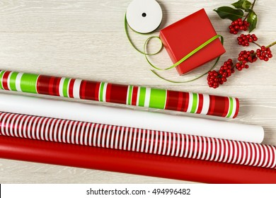 Red and green Christmas gift wrapping supplies. Wrapping paper, gift box, present, ribbons and natural botanical holly berries.