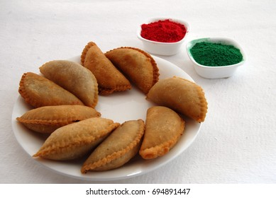 red green color powder and sweets gujia for holi festival in India