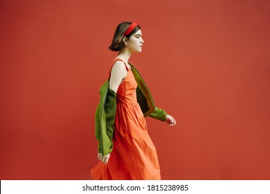 Red and green fancy clothes stylish girl walking. Looking side. profile. purposefully go to the goal. confident look. red wall background. Beautiful new wave young generation Zoomers laid back mood