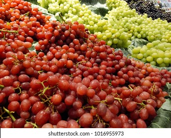 Red and green grapes for sale at a market stall.